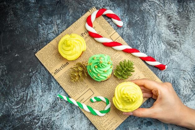 Bovenaanzicht mini cupcakes cupcake in vrouw hand kerst ornamenten op krant op donkere ondergrond