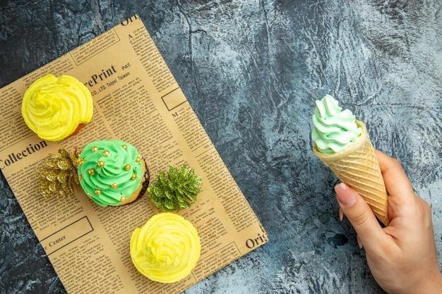Bovenaanzicht mini cupcakes kerst ornamenten op krantenijs in vrouwelijke hand op donkere ondergrond