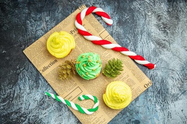 Bovenaanzicht mini cupcakes kerst ornamenten snoepjes op krant op donkere ondergrond