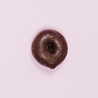 Bovenaanzicht mini geglazuurde donut op roze achtergrond