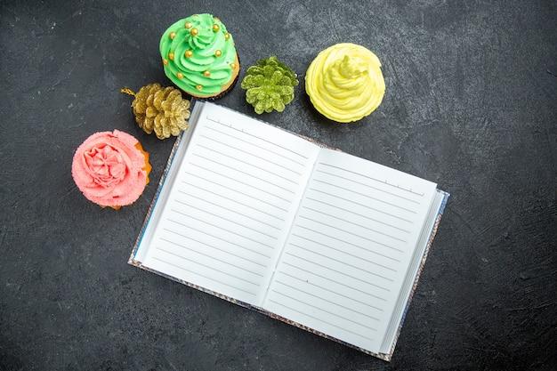 Bovenaanzicht mini kleurrijke cupcakes en een notitieboekje op donkere ondergrond