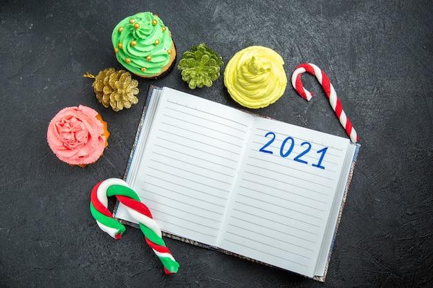 Bovenaanzicht mini kleurrijke cupcakes geschreven op notebook xmas snoepjes en ornamenten op donkere achtergrond