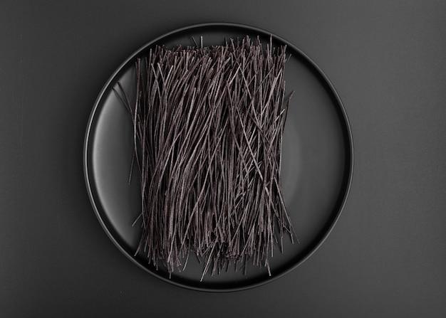 Bovenaanzicht minimalistische plaat met zwarte spaghetti