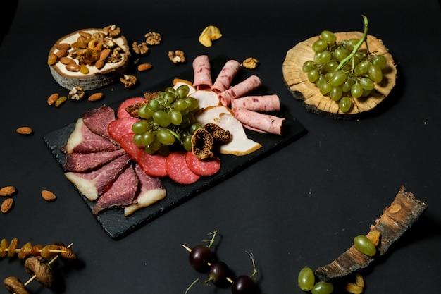 Bovenaanzicht misnaya plaat met druiven en noten op een stand met gedroogde vruchten op een zwarte tafel
