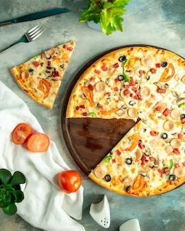 Bovenaanzicht mix pizza met kip worstjes champignons en olijven op het bord