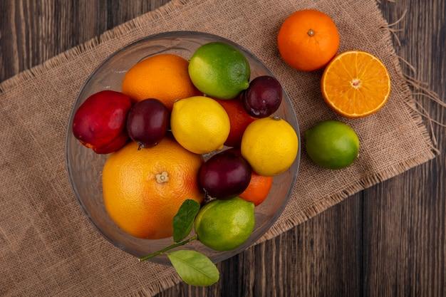 Bovenaanzicht mix van fruit citroenen limoenen pruimen perziken en sinaasappels in een vaas op een beige servet