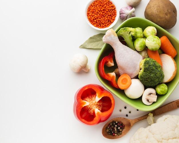 Bovenaanzicht mix van groenten in kom en kip drumstick met kopie ruimte