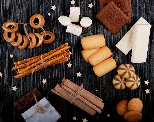 Bovenaanzicht mix van koekjes met muffins wafels marshmallows en brood stokken op een zwarte houten achtergrond