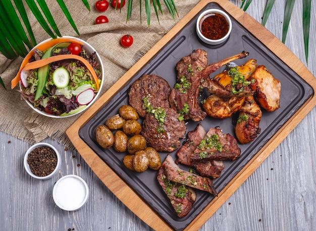 Bovenaanzicht mix van steaks met aardappelen groentesalade en saus