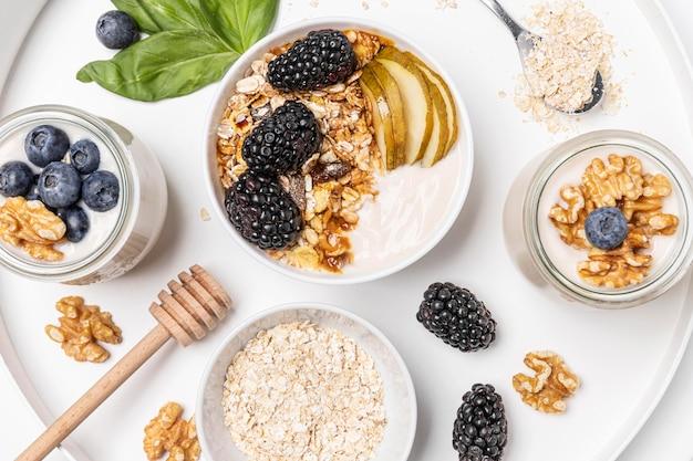 Bovenaanzicht mix van yoghurt met haver, fruit en honing op plaat