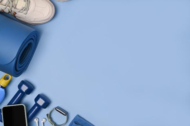 Bovenaanzicht mock-up mobiele telefoon en fitnessapparatuur op blauwe mat.
