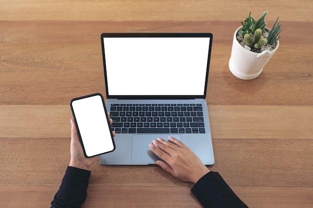 Bovenaanzicht mockup afbeelding van een handen met een leeg wit scherm mobiele telefoon en laptop op houten tafel in kantoor