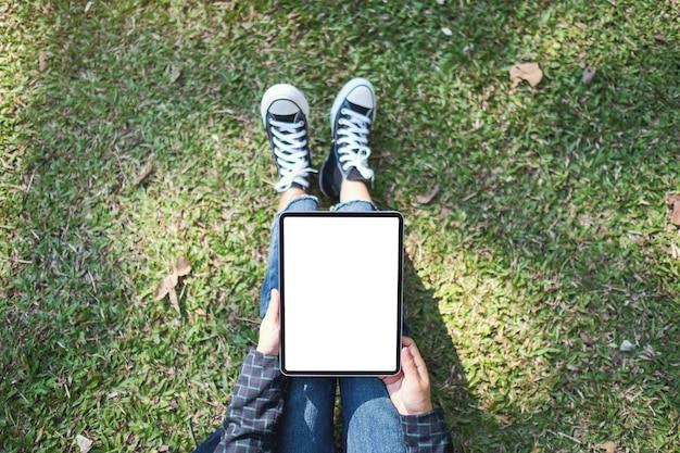 Bovenaanzicht mockup-afbeelding van een vrouw die een zwarte tablet-pc vasthoudt en gebruikt met een leeg wit bureaubladscherm terwijl ze buiten zit