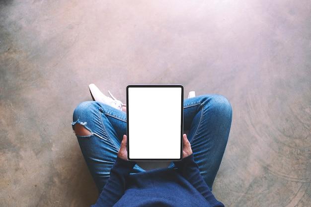 Bovenaanzicht mockup-afbeelding van een vrouw die een zwarte tablet-pc vasthoudt met een leeg wit scherm terwijl ze op de grond zit Premium Foto