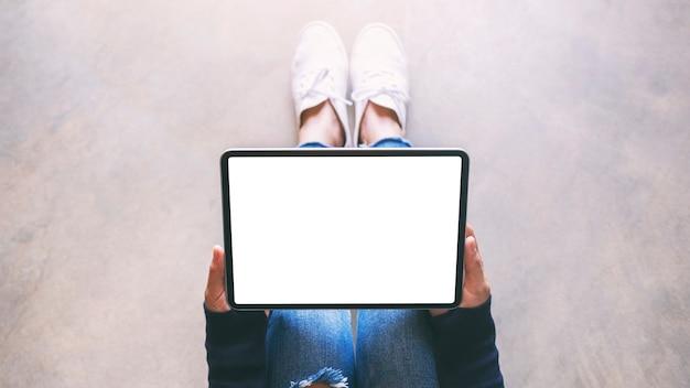 Bovenaanzicht mockup-afbeelding van een vrouw die een zwarte tablet-pc vasthoudt met een leeg wit scherm terwijl ze op de grond zit