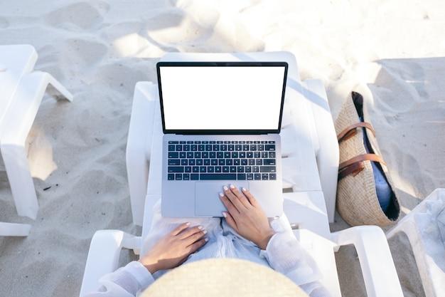 Bovenaanzicht mockup afbeelding van een vrouw die het touchpad van een laptopcomputer gebruikt en aanraakt met een leeg desktopscherm terwijl ze op een strandstoel op het strand ligt