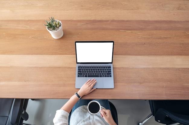 Bovenaanzicht mockup afbeelding van een vrouw met behulp van en aanraken op laptop touchpad met leeg wit bureaublad terwijl het drinken van koffie op houten tafel in kantoor