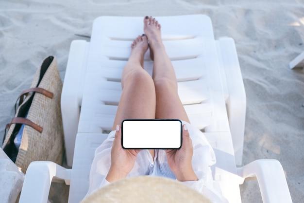 Bovenaanzicht mockup afbeelding van een vrouw met een witte mobiele telefoon met een leeg bureaublad terwijl ze op een strandstoel op het strand ligt