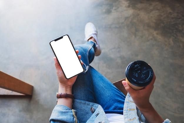 Bovenaanzicht mockup afbeelding van een vrouw met een zwarte mobiele telefoon met een leeg wit desktopscherm met koffiekopje