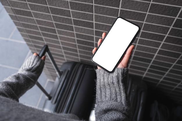 Bovenaanzicht mockup afbeelding van een vrouw met zwarte mobiele telefoon met leeg bureaublad