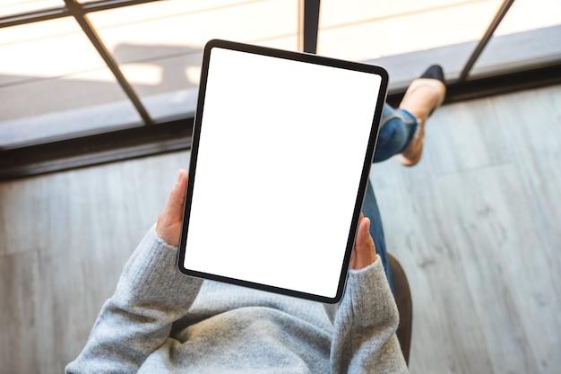 Bovenaanzicht mockup afbeelding van een vrouw met zwarte tablet pc met leeg wit scherm