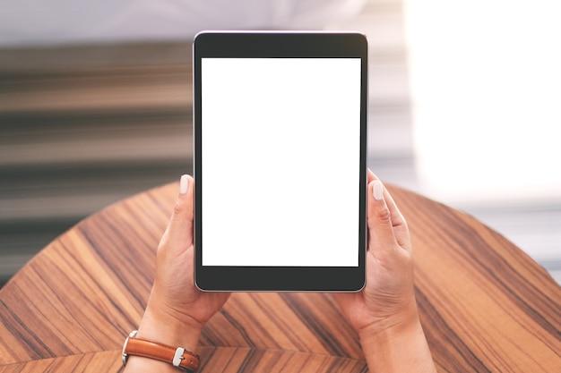 Bovenaanzicht mockup afbeelding van een vrouw zitten en houden zwarte tablet pc met leeg wit bureaublad op houten tafel