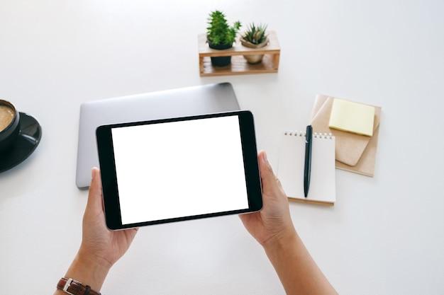 Bovenaanzicht mockup afbeelding van handen met een tablet met leeg wit scherm en laptopcomputer op houten tafel in kantoor