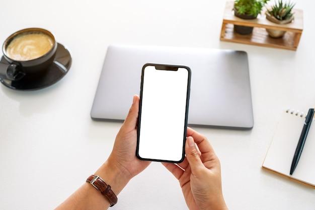 Bovenaanzicht mockup afbeelding van handen met mobiele telefoon met leeg scherm en laptopcomputer op tafel op kantoor