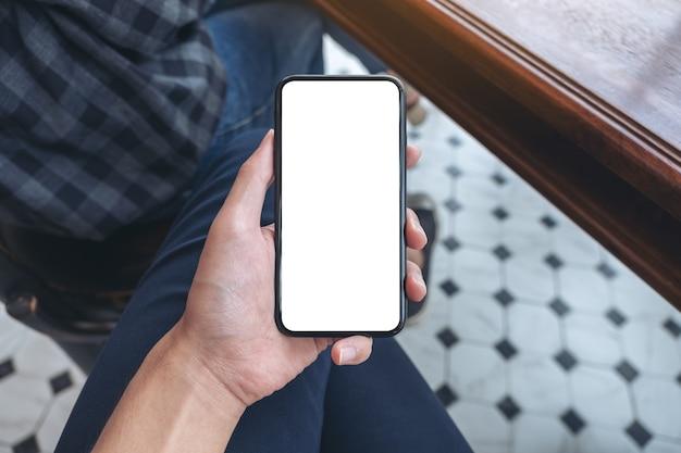 Bovenaanzicht mockup afbeelding van iemands hand met witte mobiele telefoon met leeg bureaublad op de dij in café