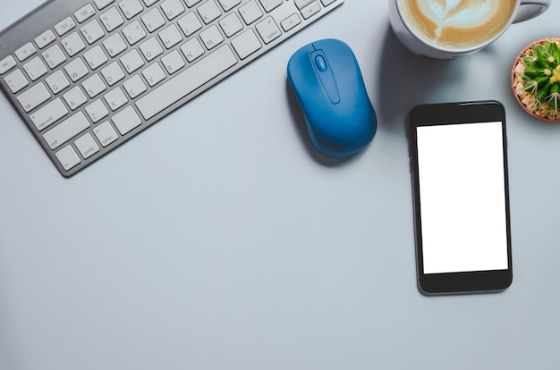 Bovenaanzicht mockup smartphone, toetsenbord, koffiemok en cactus op achtergrond. kopieer ruimte