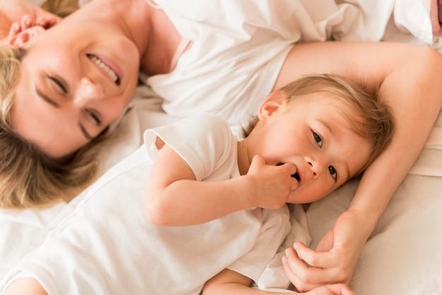 Bovenaanzicht moeder en baby zitten in bed