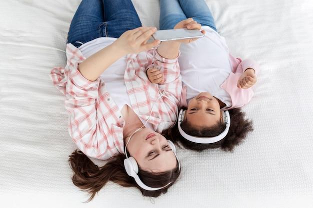 Bovenaanzicht moeder en dochter luisteren naar muziek