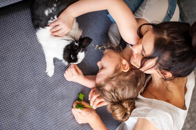 Bovenaanzicht moeder en meisje aaien klein konijn