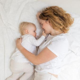 Bovenaanzicht moeder knuffelen haar babymeisje