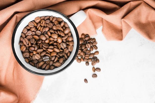 Bovenaanzicht mok met gebrande koffiebonen