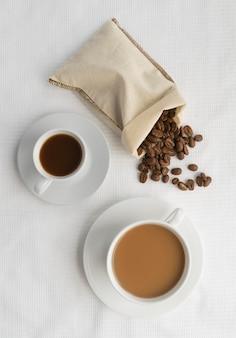 Bovenaanzicht mokken met koffie en koffie beasn ernaast