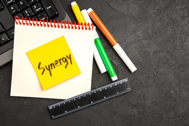 Bovenaanzicht motivatie notities met toetsenbord en potloden op donkere achtergrond pen foto notitieblok school schrijven kleur inspireren