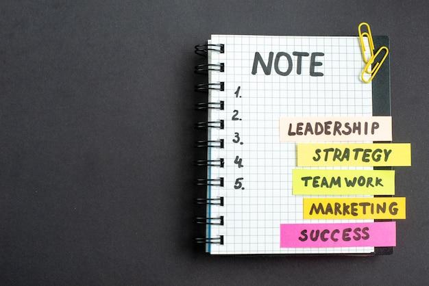 Bovenaanzicht motivatie zakelijke notities met blocnote op donkere achtergrond zakelijk werk succes baan leiderschap strategie teamwerk marketing