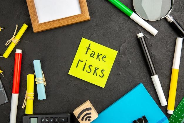 Bovenaanzicht motivatiebriefje met kleurrijke potloden en andere dingen op het donkere oppervlak