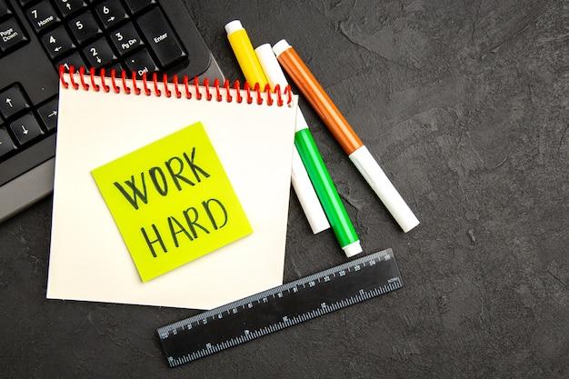 Bovenaanzicht motivatiebriefje met toetsenbord en potloden op donkere ondergrond