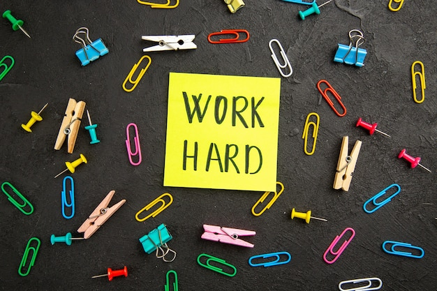 Bovenaanzicht motivatiebriefje met wasknijpers en nietjes op een donkere ondergrond wasserij foto schoolkind kleur