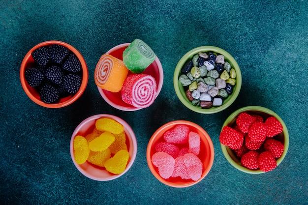 Bovenaanzicht multi-gekleurde marmelades in verschillende vormen in jam outlets op een donkergroene achtergrond