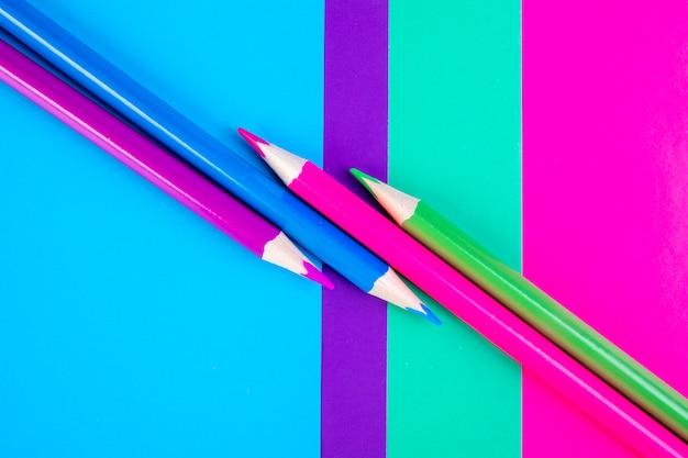 Bovenaanzicht multi-gekleurde potloden op een roze lichtgroene paarse en blauwe achtergrond