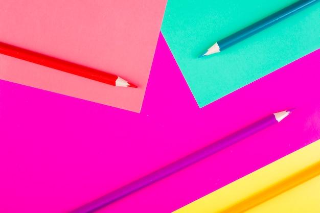 Bovenaanzicht multi-gekleurde potloden op een roze lichtgroene paarse gele achtergrond
