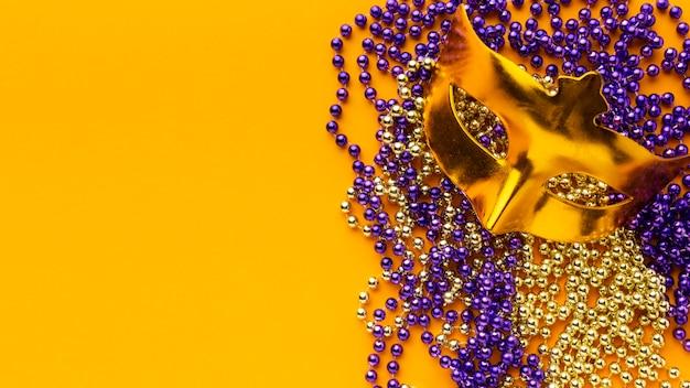 Bovenaanzicht mysterie carnaval gouden maskers en parels
