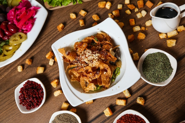 Bovenaanzicht nacho's met kaas met specerijen saus en croutons op tafel