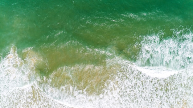 Bovenaanzicht natuur landschap van vloeiende golf witte seafoam turquoise golven prachtige tropische zee in zomer seizoen afbeelding door luchtfoto drone geschoten, hoge hoek bekijken top down.
