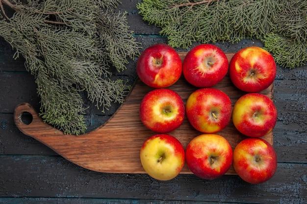 Bovenaanzicht negen vruchten negen geel-roodachtige appels op een houten snijplank op grijze tafel tussen boomtakken