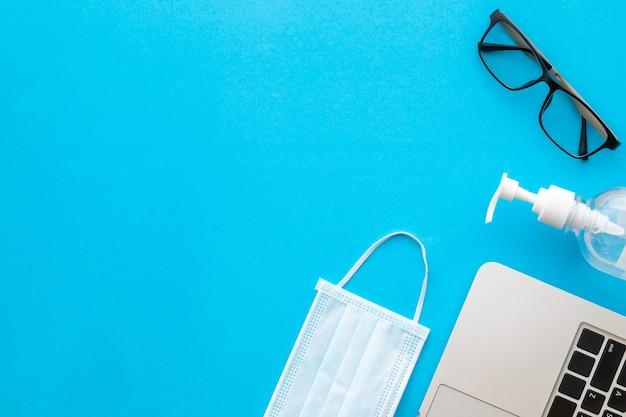 Bovenaanzicht nieuw preventief masker, ontsmettingsgel, laptop en bril. coronavirusziekte (covid-19) of gezond concept