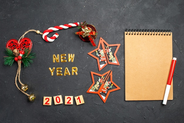 Bovenaanzicht nieuwjaar in een cirkel van verschillende kerstversieringen en rode markering op notebook op donkere geïsoleerde oppervlak